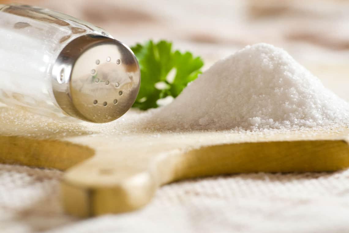 Mound of salt on a table, with salt shaker.